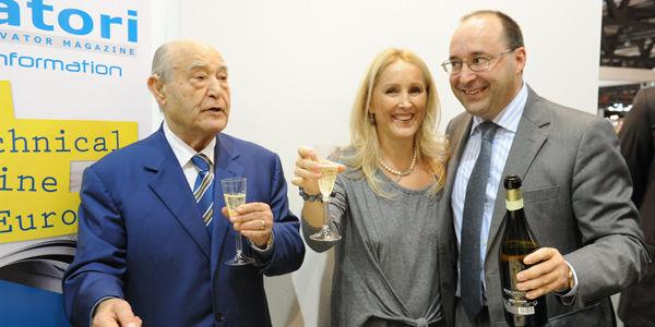Инженер Giuseppe Volpe пьет с сынами Maria и Matteo за 40 лет журнала Elevatori